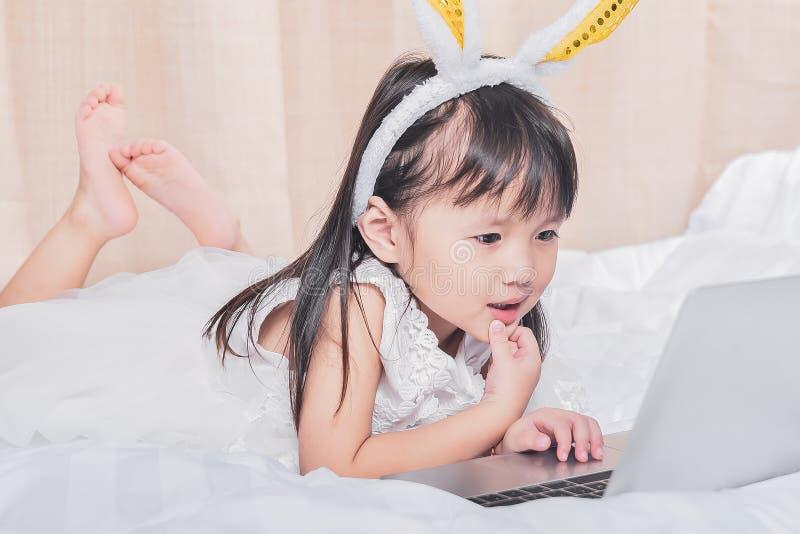 Kleines Mädchen, das mit Laptop auf dem glücklichen Lächeln des Betts unter Verwendung des Internets aufpasst und hat Spaß im Kin lizenzfreie stockbilder