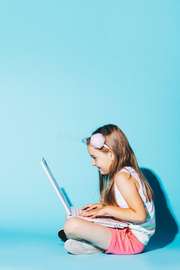 Kleines Mädchen, das mit Laptop auf ihren Knien, den Schirm betrachtend sitzt stockfotografie