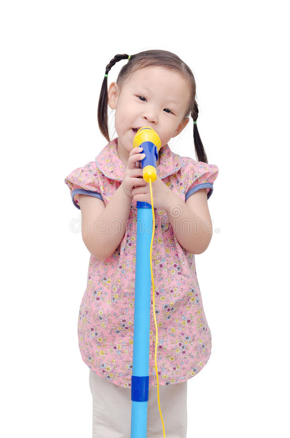 Kleines Mädchen, das mit Mikrofon singt stockfoto