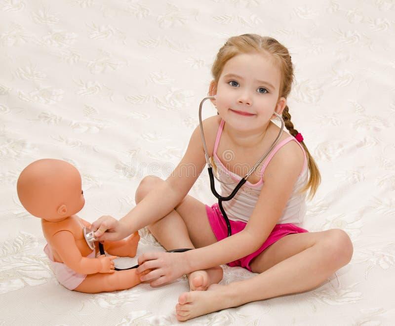 Kleines Mädchen, das mit Puppe im Krankenhaus spielt stockbilder