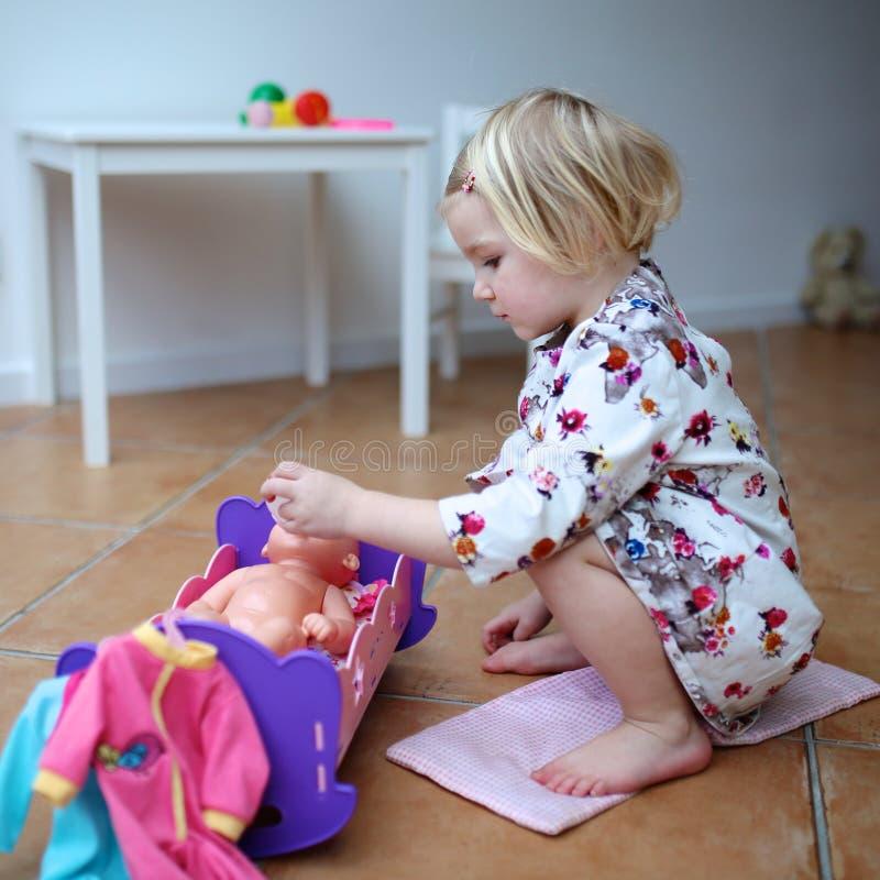 Kleines Mädchen, das mit Puppe spielt stockfotografie