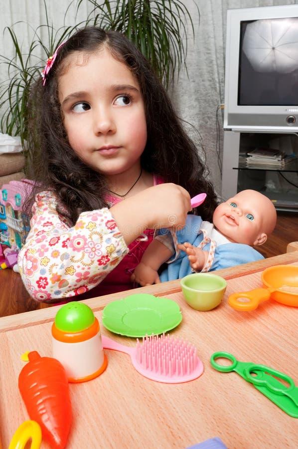 Kleines Mädchen, das mit Puppe spielt lizenzfreies stockfoto