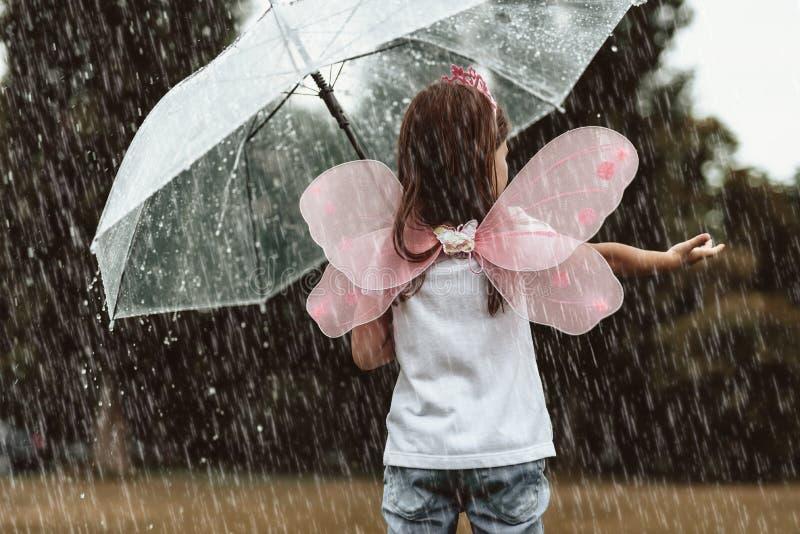 Kleines Mädchen, das mit Regen spielt lizenzfreies stockbild