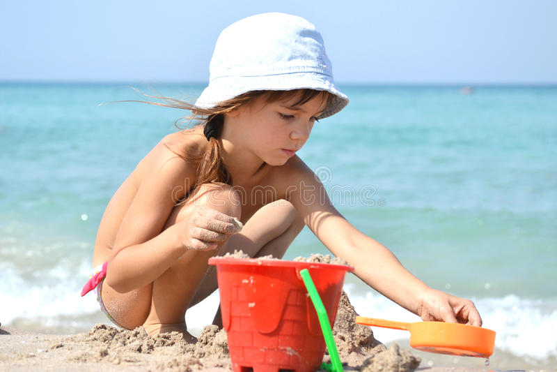 Kleines Mädchen, das mit Sand spielt lizenzfreie stockbilder