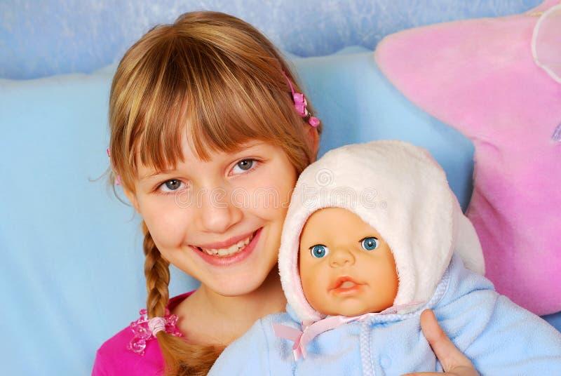 Kleines Mädchen, das mit Schätzchen - Puppe spielt stockbild
