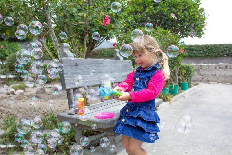 Kleines Mädchen, das mit Seifenblasen im Garten spielt stockfotos