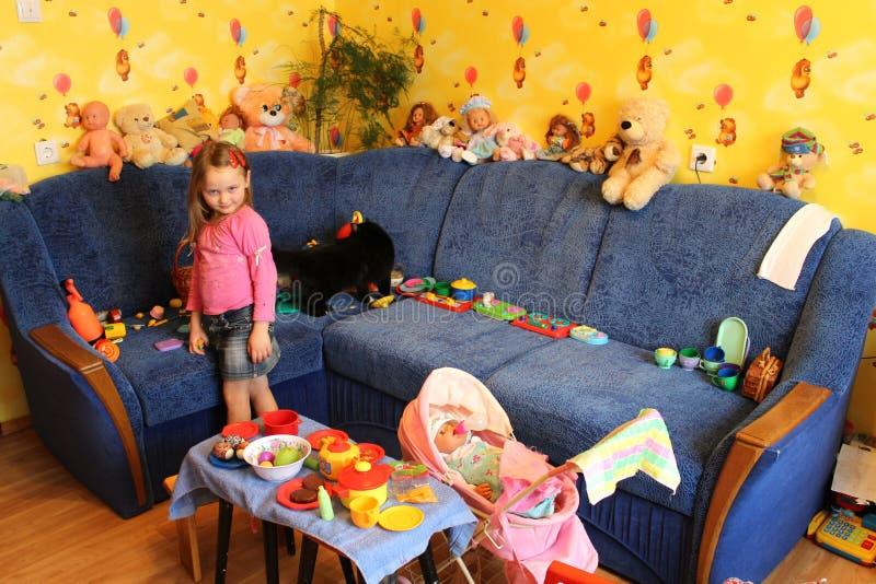 Kleines Mädchen, das mit Spielwaren in ihrem Raum spielt stockfoto