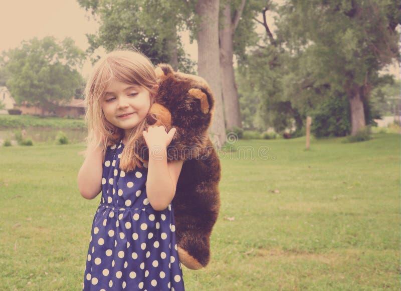 Kleines Mädchen, das mit Teddy Bear Friend im Park spielt lizenzfreie stockfotografie
