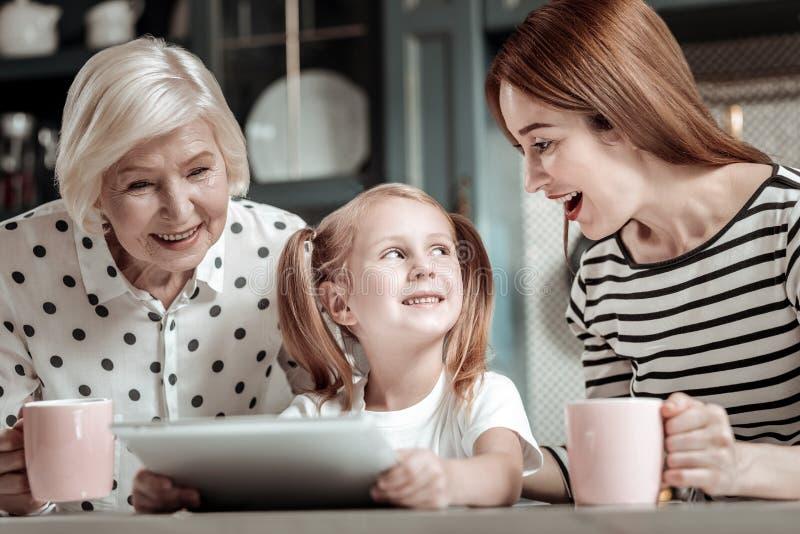 Kleines Mädchen, das moderne Tablette und ihre die Mutter schauend aufgeregt hält lizenzfreie stockfotos