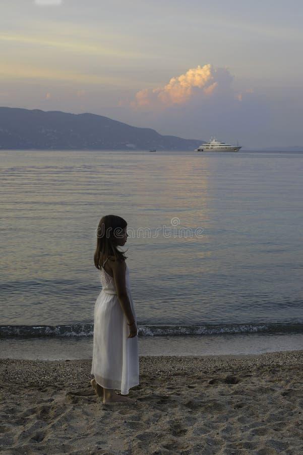 Kleines Mädchen, das nahe dem Meer auf Sonnenuntergang geht lizenzfreies stockbild