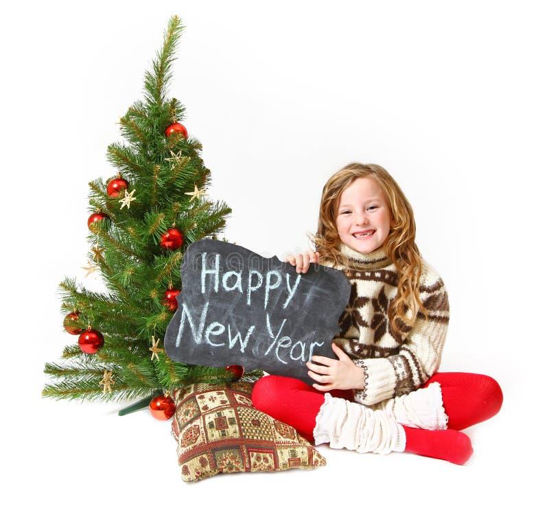 Kleines Mädchen, das nahe einem Weihnachtsbaum mit einem Zeichen mit dem w sitzt lizenzfreies stockbild
