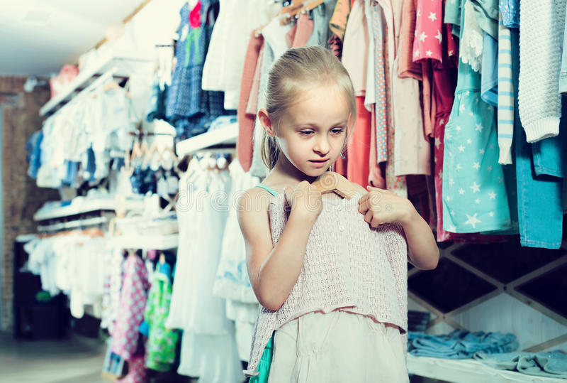 Kleines Mädchen, das neues Kleid in den Händen in der Butike hält lizenzfreies stockbild
