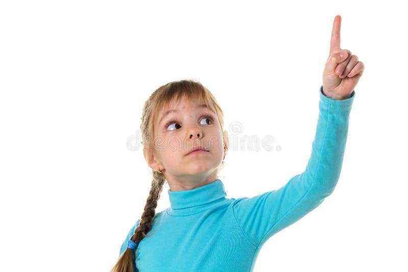 Kleines Mädchen, das oben ihren Finger, lokalisiert auf weißer Landschaft zeigt stockbild