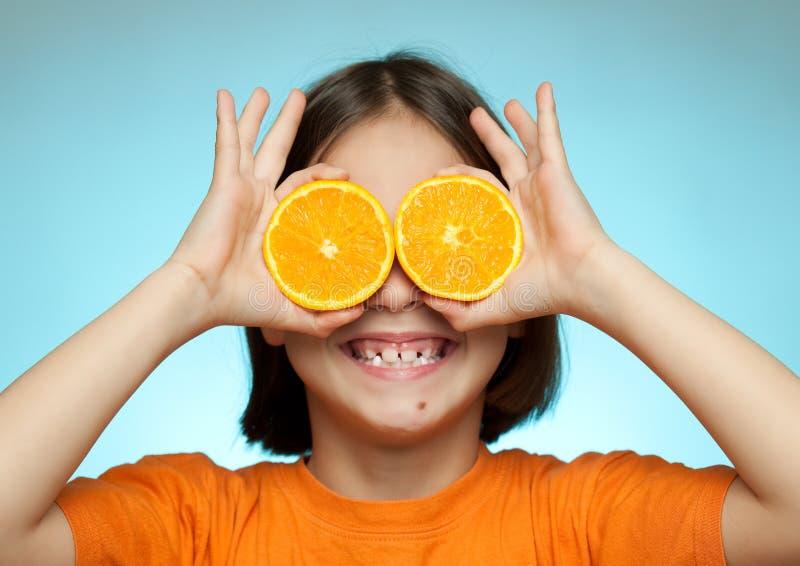 Kleines Mädchen, das Orangen als Gläser verwendet stockfoto
