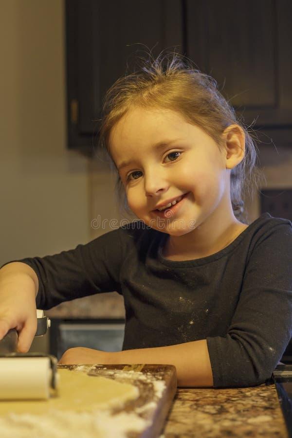 Kleines Mädchen, das Plätzchen bildet stockbild