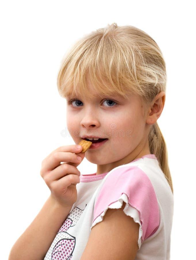 Kleines Mädchen, das Plätzchen isst stockfotografie