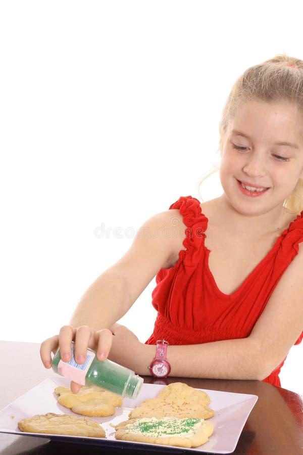 Kleines Mädchen, das Plätzchen verziert lizenzfreie stockfotos
