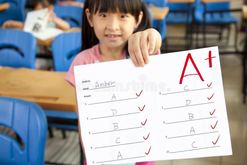Kleines Mädchen, das Prüfungpapier zeigt lizenzfreie stockfotografie