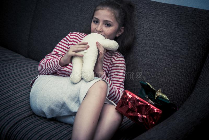 Kleines Mädchen, das Puppe in der dunklen Ecke des Raumes isst lizenzfreie stockfotografie