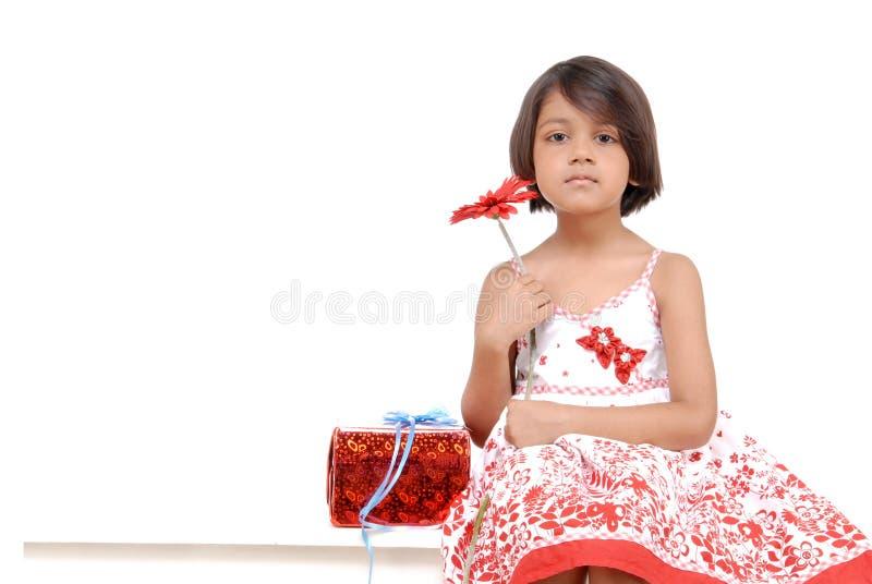 Kleines Mädchen, das rote Blume anhält stockbilder