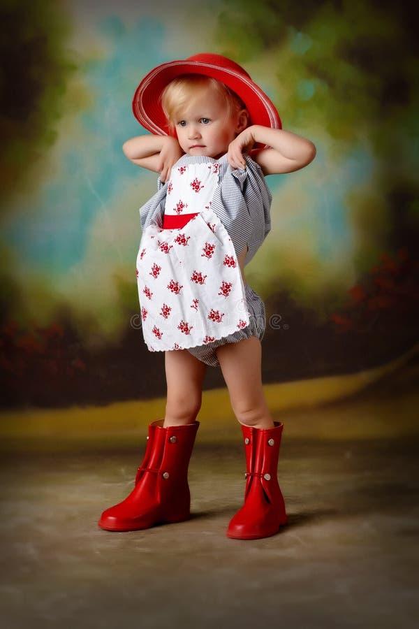 Kleines Mädchen, das in rotes Kleid ausdehnt stockfoto