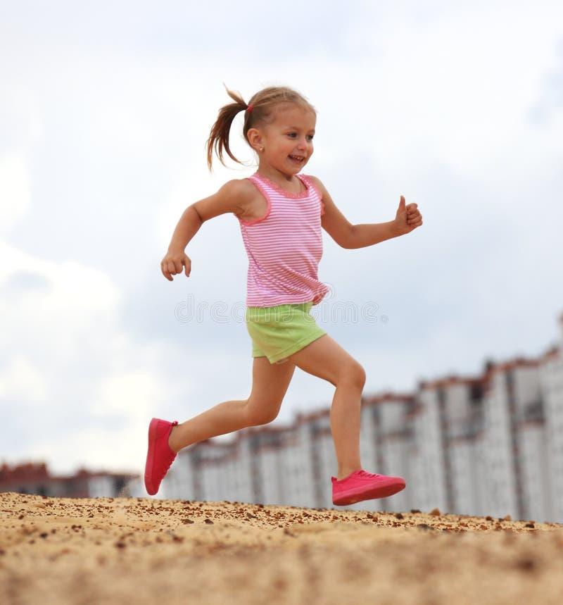 Kleines Mädchen, das in Sand läuft stockbilder