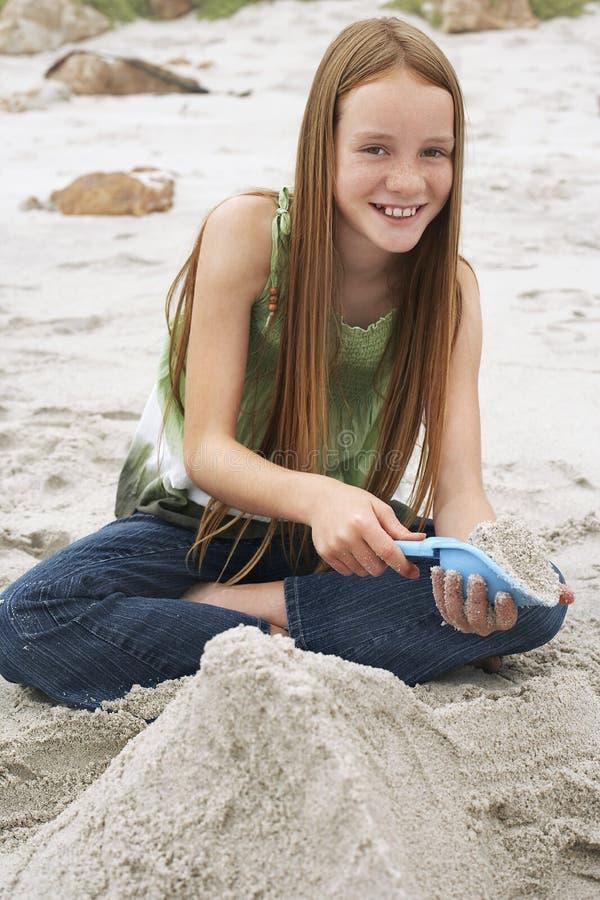 Kleines Mädchen, das Sandburg am Strand macht stockbilder