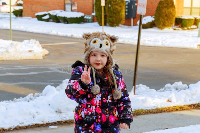 Kleines Mädchen, das Schnee auf Haupt-Antriebsweise schaufelt Schöner schneebedeckter Garten oder Vorgarten stockfoto