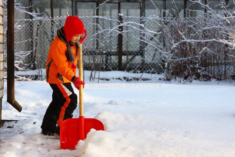 Kleines Mädchen, das Schnee mit Schaufel schaufelt lizenzfreie stockfotografie