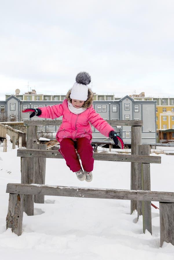 Kleines Mädchen, das in Schnee springt stockfotografie