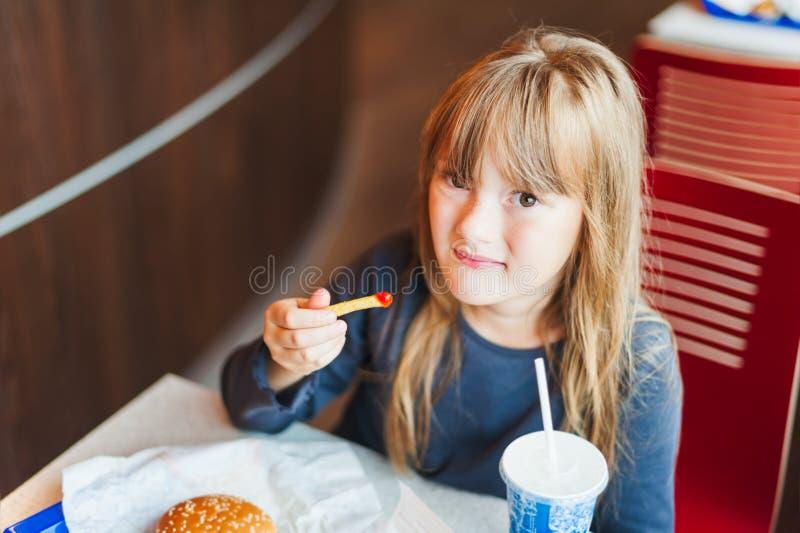 Kleines Mädchen, das Schnellimbiß in einem Café isst stockfotos