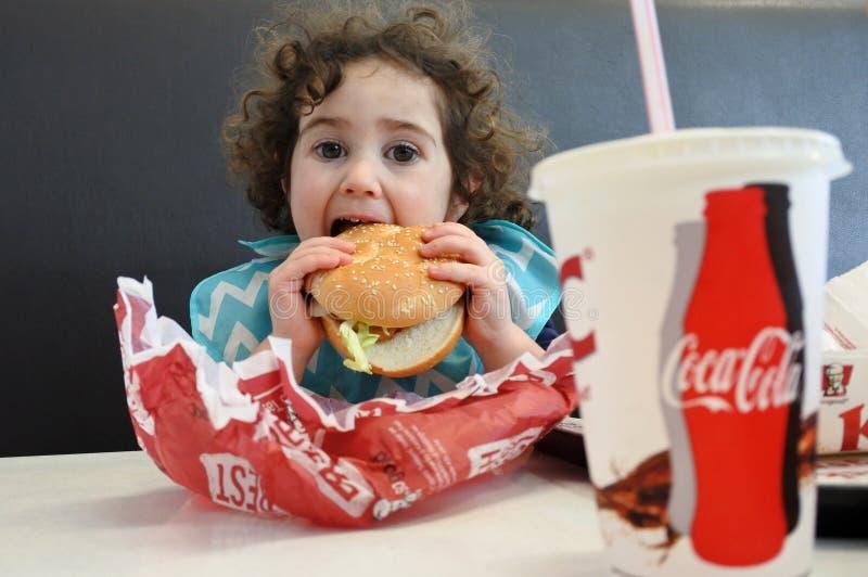 Kleines Mädchen, das Schnellimbiß isst stockfotos