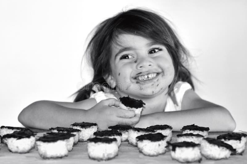 Kleines Mädchen, das Schokoladenplätzchen essend gefasst wird stockfotos