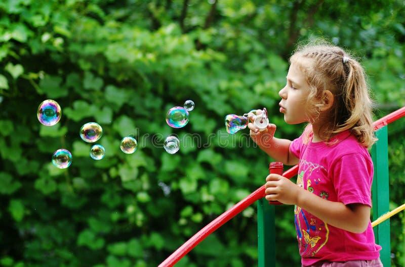Kleines Mädchen, das Seifenluftblasen bildet stockbilder