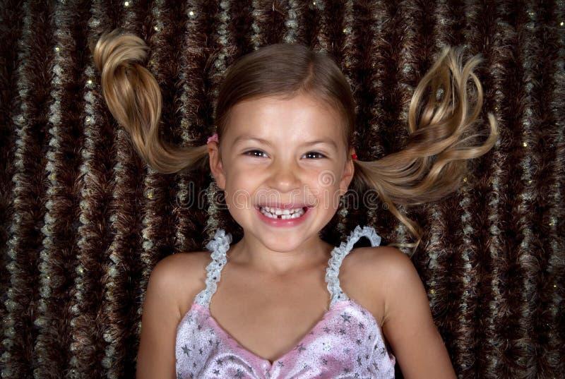 Kleines Mädchen, das sich auf einer Wolldecke und einem Lächeln hinlegt lizenzfreies stockfoto