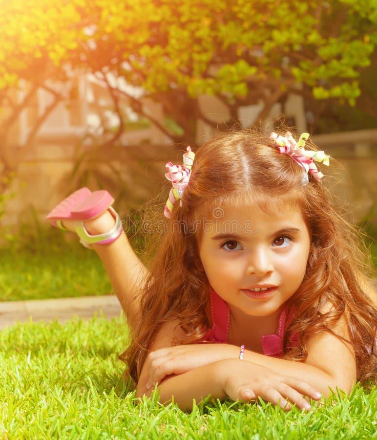 Kleines Mädchen, das sich auf grünem Gras hinlegt stockbilder