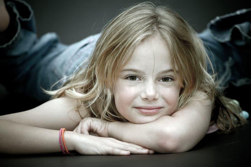 Kleines Mädchen, das sich, lächelnd hinlegt stockbild
