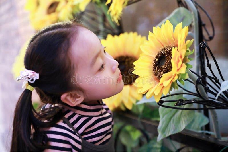 Kleines Mädchen, das Sommer-Blumen schaut stockbilder