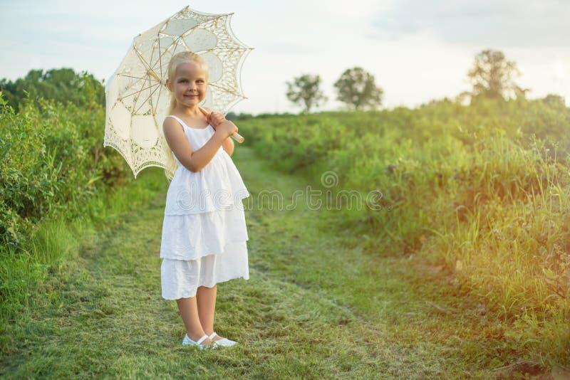 Kleines Mädchen, das Sonnenschirm im Sommer hält stockfotos