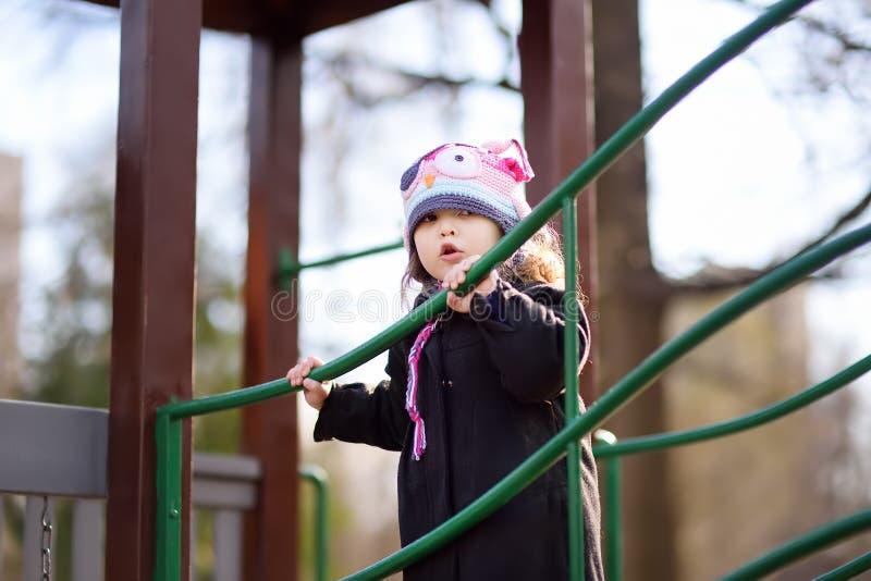 Kleines Mädchen, das Spaß auf Spielplatz im Freien am Frühlings- oder Herbsttag hat stockfotos