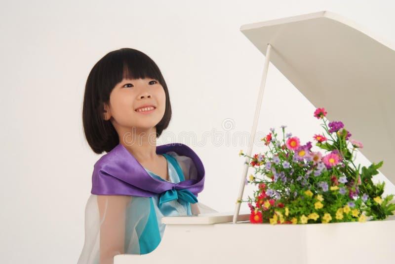 Kleines Mädchen, das Spielzeugklavier spielt stockbild