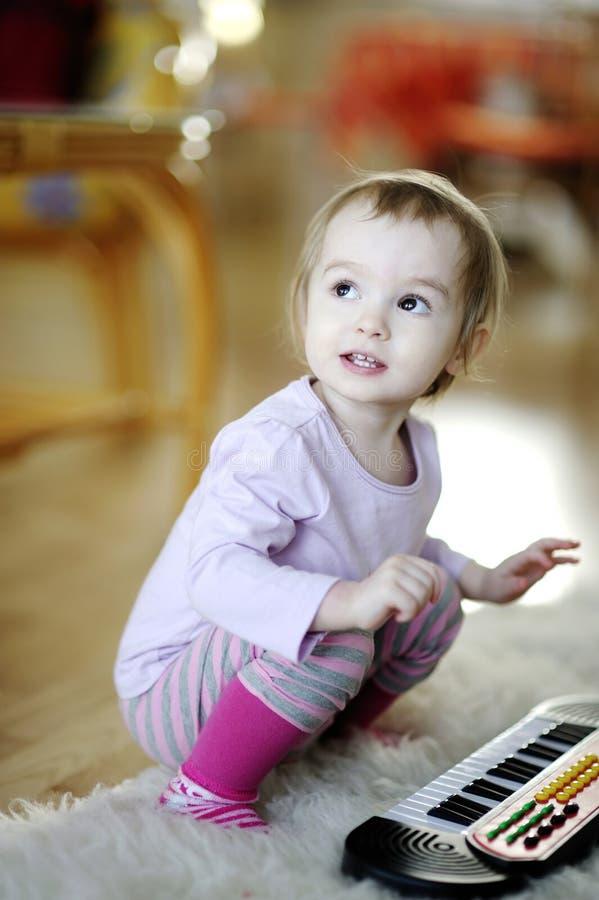 Kleines Mädchen, das Spielzeugklavier spielt stockbilder