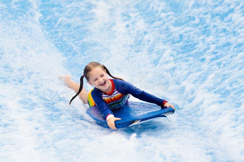Kleines Mädchen, das in Strandwellensimulator surft stockfotografie