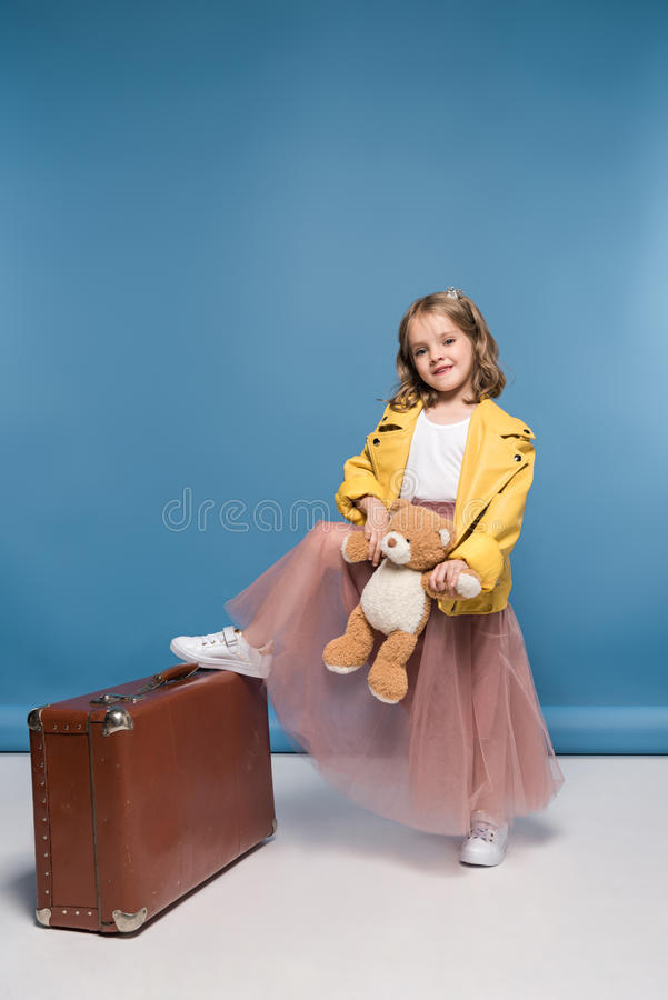 Kleines Mädchen, das Teddybären hält und mit Koffer im Studio aufwirft stockfoto