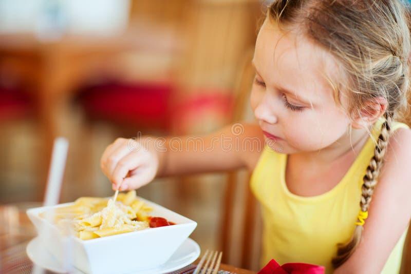 Kleines Mädchen, das Teigwaren isst stockfoto