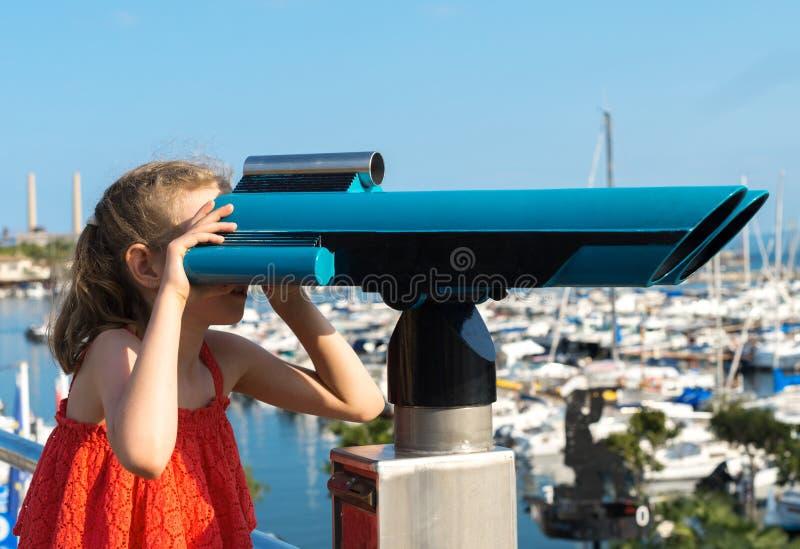Kleines Mädchen, das Teleskop verwendet stockbild