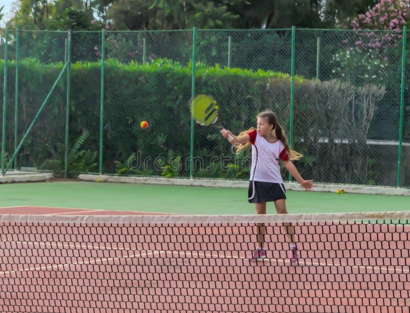 Kleines Mädchen, das Tennis auf dem Gericht spielt stockfotografie