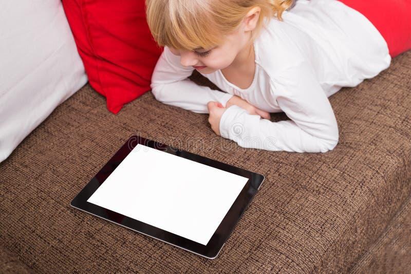 Kleines Mädchen, das tragbares Gerät verwendet stockbilder