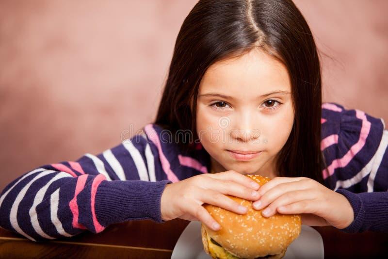 Kleines Mädchen, das ungesunde Fertigkost isst stockbild