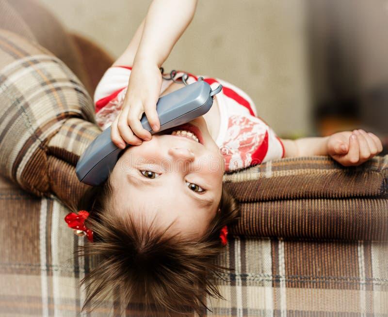 Kleines Mädchen, das unten liegt, sprechend an einem verdrahteten Telefon lizenzfreie stockbilder